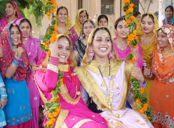 Punjabi young girls Wearing Colorful Dresses Performs Punjabi Traditional Folk Dance Gidda and enjoying ride on swing at a college in Amritsar on Friday, during the celebration of Teej festival of monsoon. File PHOTO-PRABHJOT GILL AMRITSAR