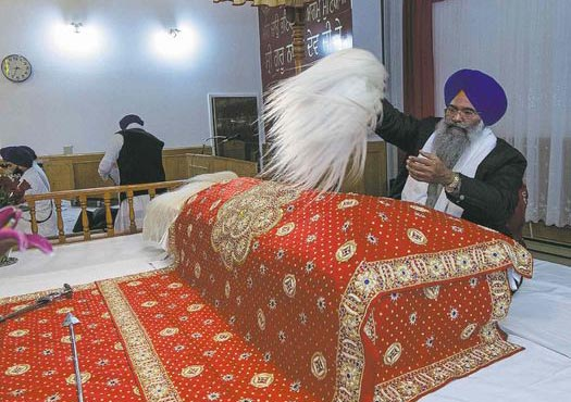 A member of the congregation at the Sikh Society of Manitoba waves a whisk over the Guru Granth Sahib Thursday