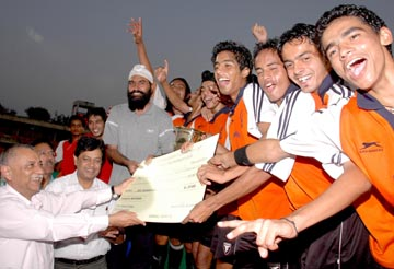 The jubilant Chandigarh Hockey Academy players receiving trophy and cheque of Rs 50,000 from Adviser to the Chandigarh Administrator Pradip Mehra in Chandigarh on Wednesday.